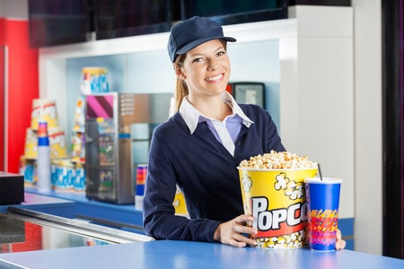 concession: Confident Worker With Popcorn And Drink At Concession Stand