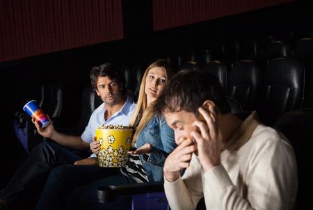 pareja enojada: Pares enojados Mirando a Hombre que usa el m�vil en teatro