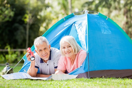 staycation: Senior Couple With Map And Torch In Tent