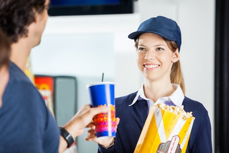 selling service smile: Happy Worker Selling Popcorn And Drink To Man At Cinema Stock Photo