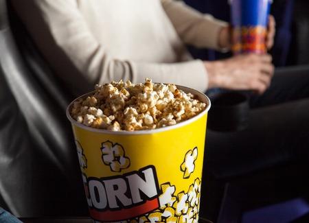 popcorn: Cubo de palomitas Con El Hombre Sentado En Teatro