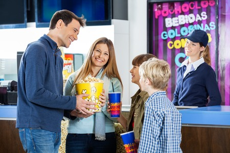 concession: Happy Family Having Snacks At Cinema Concession Stand