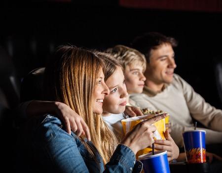 zábava: Čtyřčlenná rodina sledování filmu v divadle Reklamní fotografie