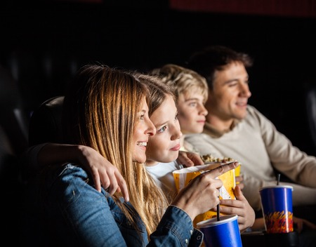 family movies: Family Of Four Watching Movie In Theater