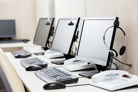 centro de computo: Computadoras Con Los Auriculares En El Escritorio Foto de archivo