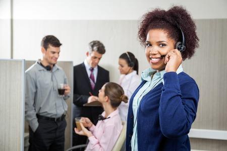 Smiling Female Customer Service Representative Holding Headphone Foto de archivo