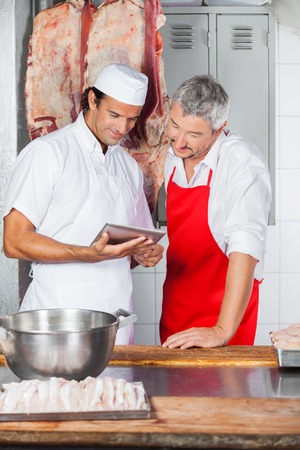 prime adult: Butchers Using Tablet Computer Together In Butchery