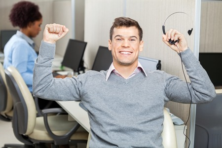 Customer Service Representative With Arms Raised Holding Headset photo