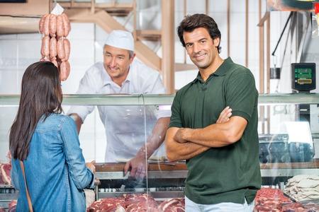 carniceria: Hombre Feliz Con La Mujer En La compra de Carne Carnicería Foto de archivo