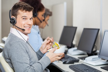 call centre girl: Male Customer Service Representative Having Food In Office