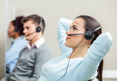 Relaxed Female Customer Service Representative Wearing Headset A photo