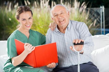 Usmívající se žena zdravotní sestra a starší muž s knihou
