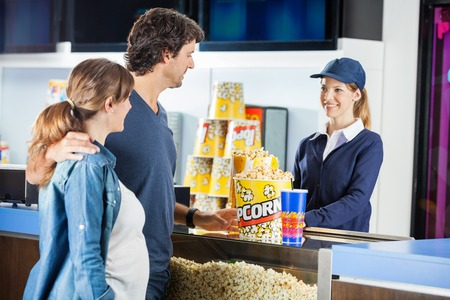 dessert stand: Expectant Couple Buying Popcorn At Cinema Concession Stand