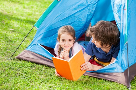 camping tent: Happy Girl With Brother Reading Book In Tent