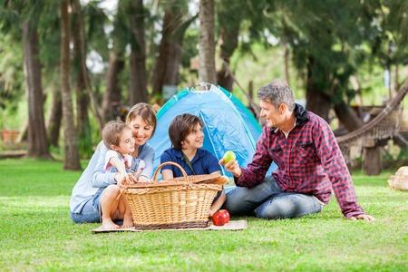 viaje familia: Familia con Picnic Basket En Camping Foto de archivo