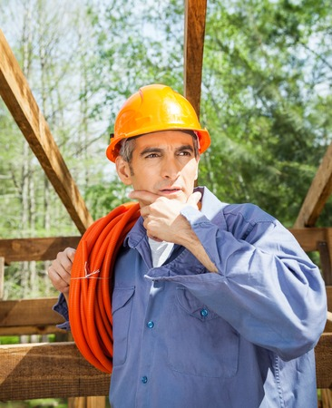 hand on the chin: Thoughtful Construction Worker With Hand On Chin Stock Photo
