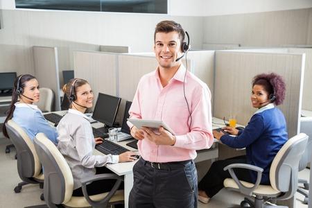 centro de computo: Ejecutivo de Servicio al Cliente que sostiene la tablilla Ordenador En Call Cente Foto de archivo