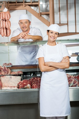 Butchers At Display Cabinet In Butchery photo