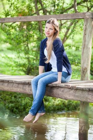 piedi nudi di bambine: Bella donna seduta sul ponte di legno