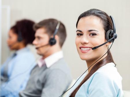 Usmívající se žena zákazníkům služby reprezentativní v kanceláři Reklamní fotografie