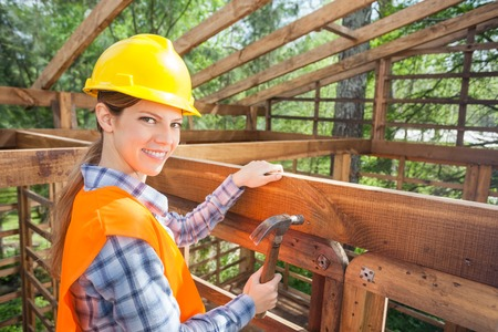 timber frame: Happy Female Worker Hammering Nail On Timber Frame