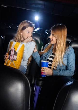 girl bonding: Mother Consoling Scared Daughter In Cinema Theater