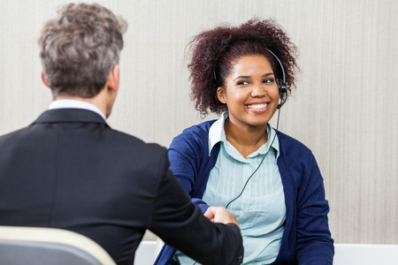 Young Female Customer Service Agent Shaking Hands With Manager photo