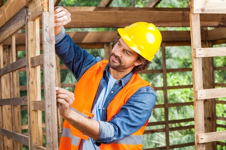 timber frame: Construction Worker Measuring Timber Frame