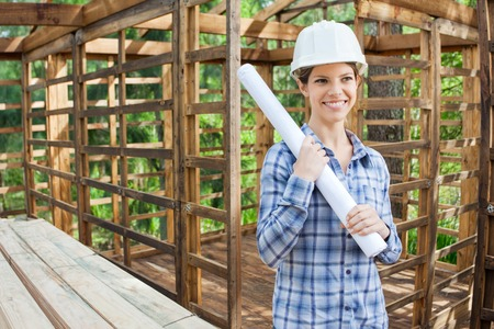 Happy Engineer Holding Blueprint In Wooden Cabin photo
