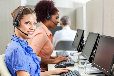 customer service phone: Happy Customer Service Agent Using Computer At Office