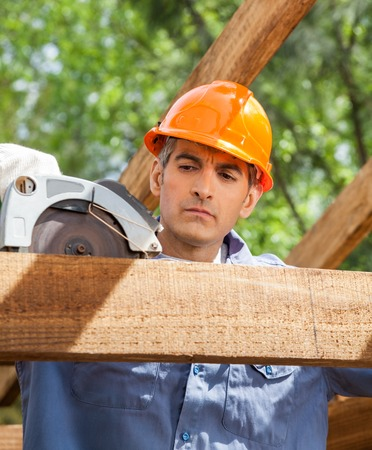 timber frame: Construction Worker Using Electric Saw On Timber Frame Stock Photo