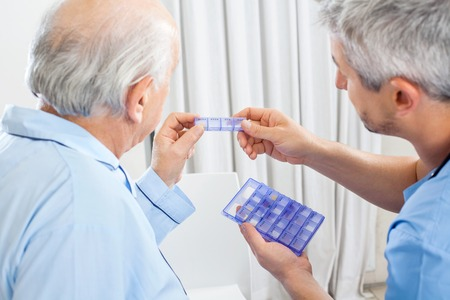 check up: Caretaker Showing Prescription Medicine To Senior Man Stock Photo