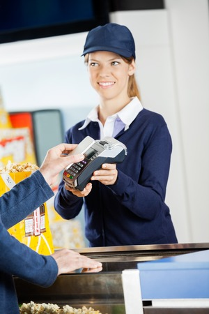 accepting: Smiling Worker Accepting Payment Through NFC Technology At Cinem