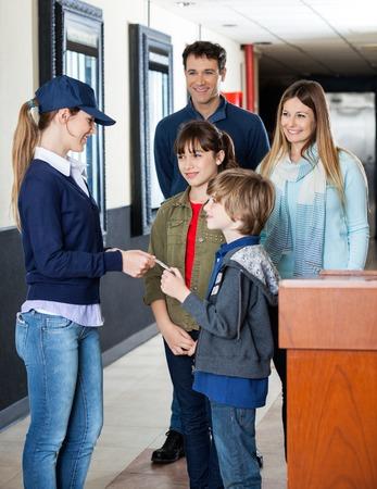 Ragazzo che dà biglietto per lavoratrice per l'esame mentre la famiglia in attesa in coda al cinema photo