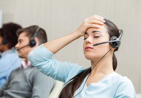 to phone calls: Tired Female Customer Service Agent In Call Center Stock Photo