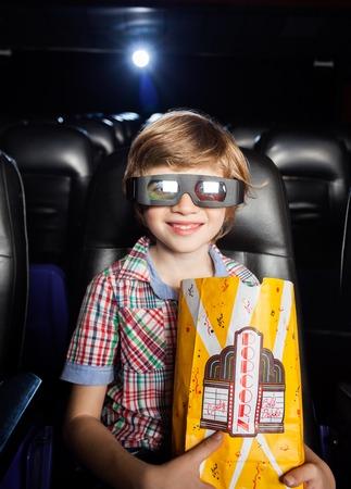 Ragazzo sorridente che tiene Popcorn In Theater 3D photo