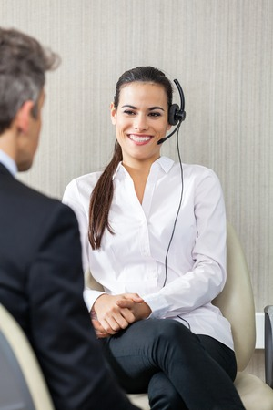 head set: Female Customer Service Agent Looking At Manager Stock Photo