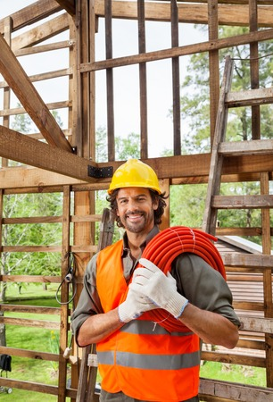 incomplete: Happy Worker Holding Pipe In Incomplete Wooden Cabin
