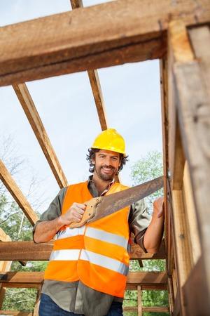 serrucho: Trabajador sonriente del corte de madera con serrucho En Sitio