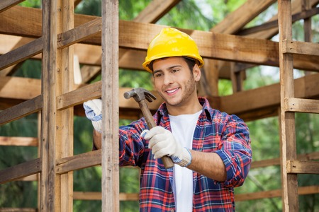 hammering: Worker Hammering Nail On Wooden Cabin Stock Photo