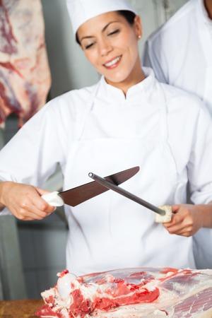 holding a knife: Female Butcher Sharpening Knife Stock Photo