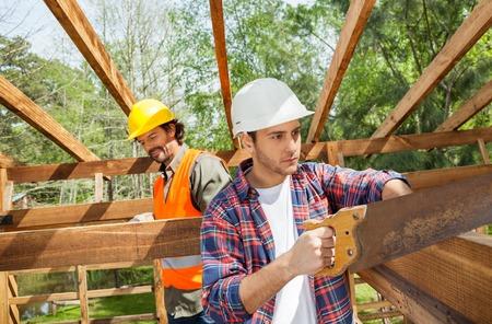 serrucho: Trabajador de construcción de cortar madera con serrucho En Sitio