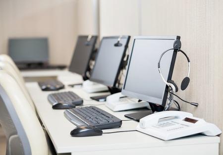 centro de computo: Ordenadores con los auriculares en el lugar de trabajo