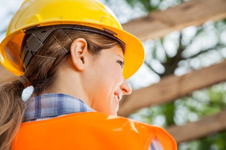 Rear view of female construction worker looking away at site photo