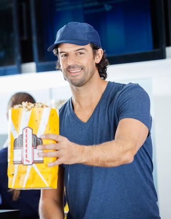 concession: Smiling Male Worker Offering Popcorn At Concession Stand Stock Photo