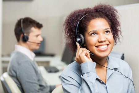 Happy Female Call Center Agent Using Headset In Call Center