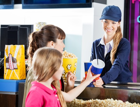 selling service smile: Sisters Buying Snacks From Concession Worker At Cinema Stock Photo