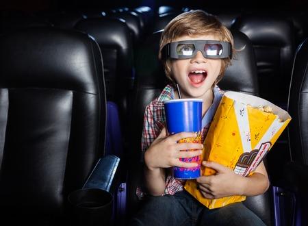 映画館で 3 D 映画を見て驚く少年 写真素材