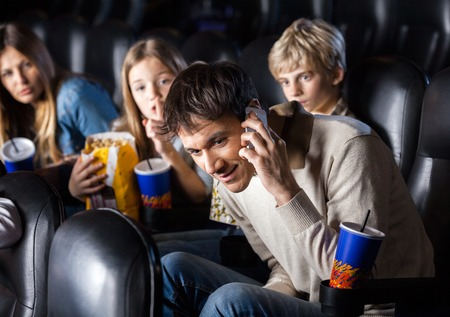 Family Looking At Man Using Mobilephone In Theater Stock Photo