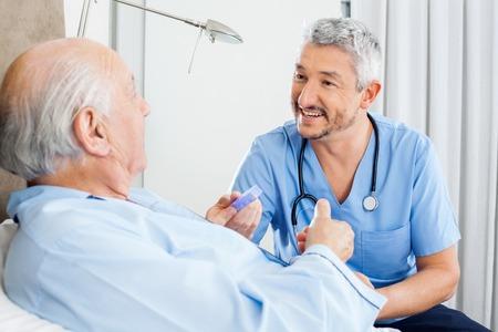Happy Caretaker Discussing Prescription With Senior Man Foto de archivo